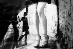 Silhouette of a woman in a dark alley of the city. Women`s feet in heels in a dark alley of the city, Women`s feet in heels in a dark alley of the city royalty free stock photos