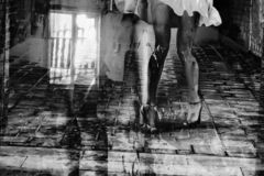 Silhouette of a woman in a dark alley of the city. Women`s feet in heels in a dark alley of the city, Women`s feet in heels in a dark alley of the city royalty free stock photo