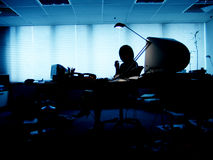 Silhouette of a woman in a dark office. A woman sitting in a dark office with a lamp on Stock Photography