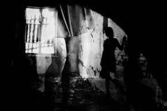 Silhouette of a woman in dark room. Women`s feet in heels in a dark alley of the city, Women`s feet in heels in a dark alley of the city royalty free stock photo