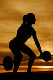 Silhouette of a woman deadlifting looking to side Stock Image