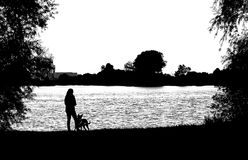 Silhouette of woman and dog Stock Image