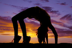 Silhouette of woman doing back bend Stock Photography