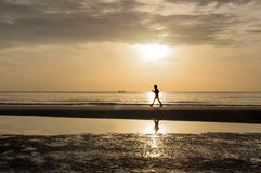 Silhouette of woman doing a brisk walking on the beach at sunset Stock Photography