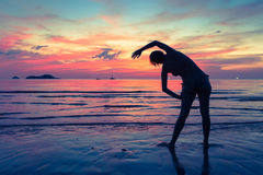 Silhouette of woman doing exercises on the evening sea beach. Stock Images