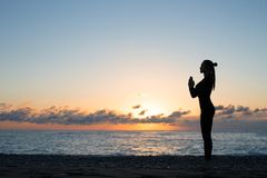 Silhouette of woman doing greeting to the sun on the beach at sunrise, morning yoga royalty free stock images