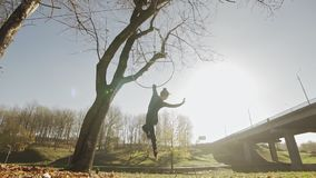 Silhouette of woman doing some acrobatic elements on aerial hoop outdoors stock footage