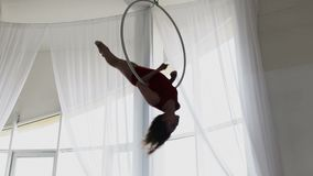 Silhouette of woman doing some acrobatic elements on aerial hoop.  stock footage