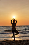 Silhouette of woman doing yoga on a beach at sunset Royalty Free Stock Photography