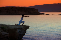 Silhouette of a woman doing yoga on the beach at sunset Royalty Free Stock Images