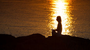 Silhouette of a woman doing yoga on the beach at sunset Stock Photography