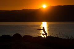 Silhouette of a woman doing yoga on the beach at sunset Royalty Free Stock Photos