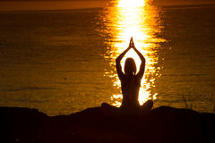 Silhouette of a woman doing yoga on the beach at sunset Stock Images