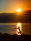 Silhouette of a woman doing yoga on the beach at sunset Royalty Free Stock Photo