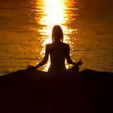 Silhouette of a woman doing yoga on the beach at sunset Royalty Free Stock Image