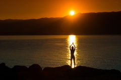 Silhouette of a woman doing yoga on the beach at sunset Royalty Free Stock Photography