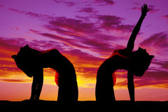 Silhouette of woman doing yoga bend back reach up Royalty Free Stock Images
