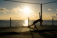 Silhouette of woman doing yoga on the dock by the sea at sunrise stock photos