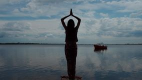 Yoga in nature. Silhouette of a woman doing yoga exercise in the morning. beautiful young girl doing a yoga pose by a lake. Yoga in the nature near the water stock video