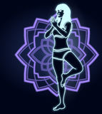 Silhouette of a woman doing yoga exercises. Neon mandala on the background. Vector image. Stock Photos