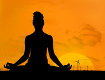 Silhouette of woman doing yoga in front of the sunset Stock Images