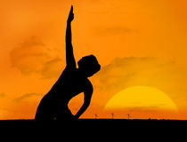 Silhouette of woman doing yoga under sunset Stock Image