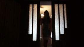 Silhouette of a woman in a doorway front of the window stock video footage