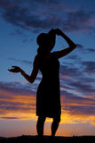 Silhouette woman in dress and heels touch hat standing Royalty Free Stock Images