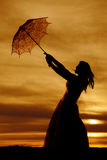 Silhouette of a woman in a dress with an umbrella blowing above Royalty Free Stock Photos