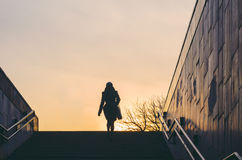 Silhouette of a woman emerging from an underpass. City life Stock Photography