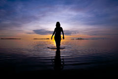 Silhouette of woman figure walking in shallow sea Stock Photos