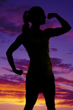Silhouette of woman fitness flex one arm look to side Stock Photography