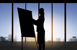 Silhouette of woman with flipboard over office Stock Photo