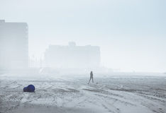 Silhouette of a woman on foggy city beach. Selective focus Royalty Free Stock Images