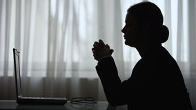 Silhouette of woman folding hands and looking at screen of laptop, thinking stock video footage