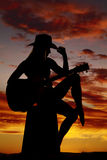 Silhouette of a woman with a guitar hand on hat Stock Photo