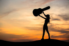 Silhouette of woman with guitar Stock Image