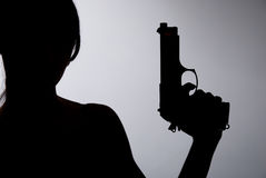 Silhouette of a woman with a gun on a gray background Stock Photography