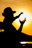 Silhouette of a woman. And hand holding the sun Stock Photos