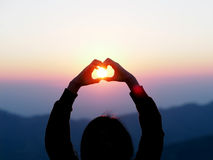 Silhouette woman hands in heart symbol shaped. Love concept with sunlight and flare at sunrise nature background Royalty Free Stock Photos