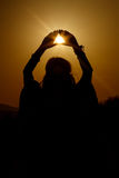 Silhouette of woman hands holding sun in triangle on background Stock Photo