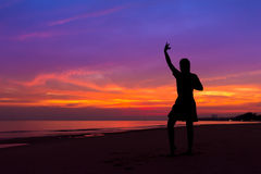 Silhouette of woman with hands up while standing on sea beach at stock photography