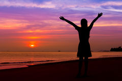 Silhouette of woman with hands up while standing on sea beach at royalty free stock photography