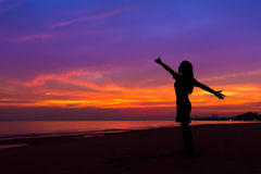 Silhouette of woman with hands up while standing on sea beach at stock photos