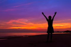 Silhouette of woman with hands up while standing on sea beach at stock image