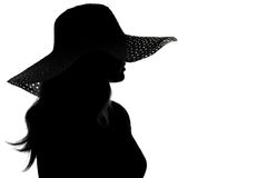 Silhouette of a woman in a hat Stock Images
