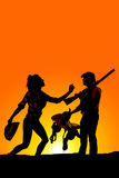 Silhouette of a woman with her hat in hand reaching up to cowboy. A silhouette of a cowgirl reaching up to her cowboy, who is holding a saddle and rifle Stock Image