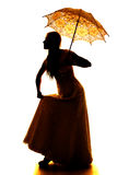 Silhouette of a woman hold skirt and umbrella stock photo