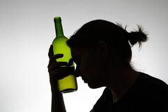 Silhouette of a woman holding a bottle Royalty Free Stock Images