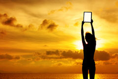 Silhouette of woman holding digital tablet Royalty Free Stock Photos